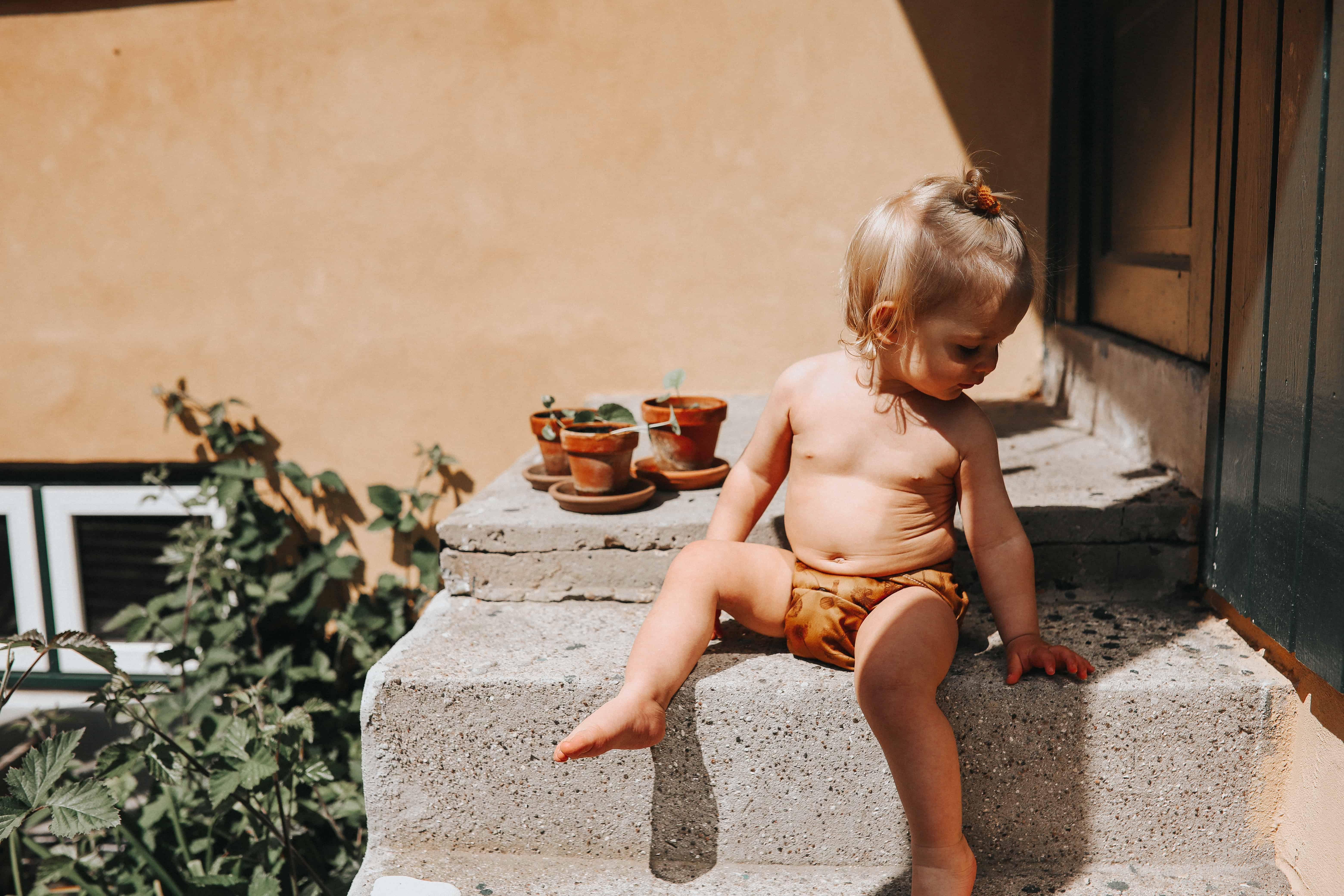 Baby på trappe med stofble på